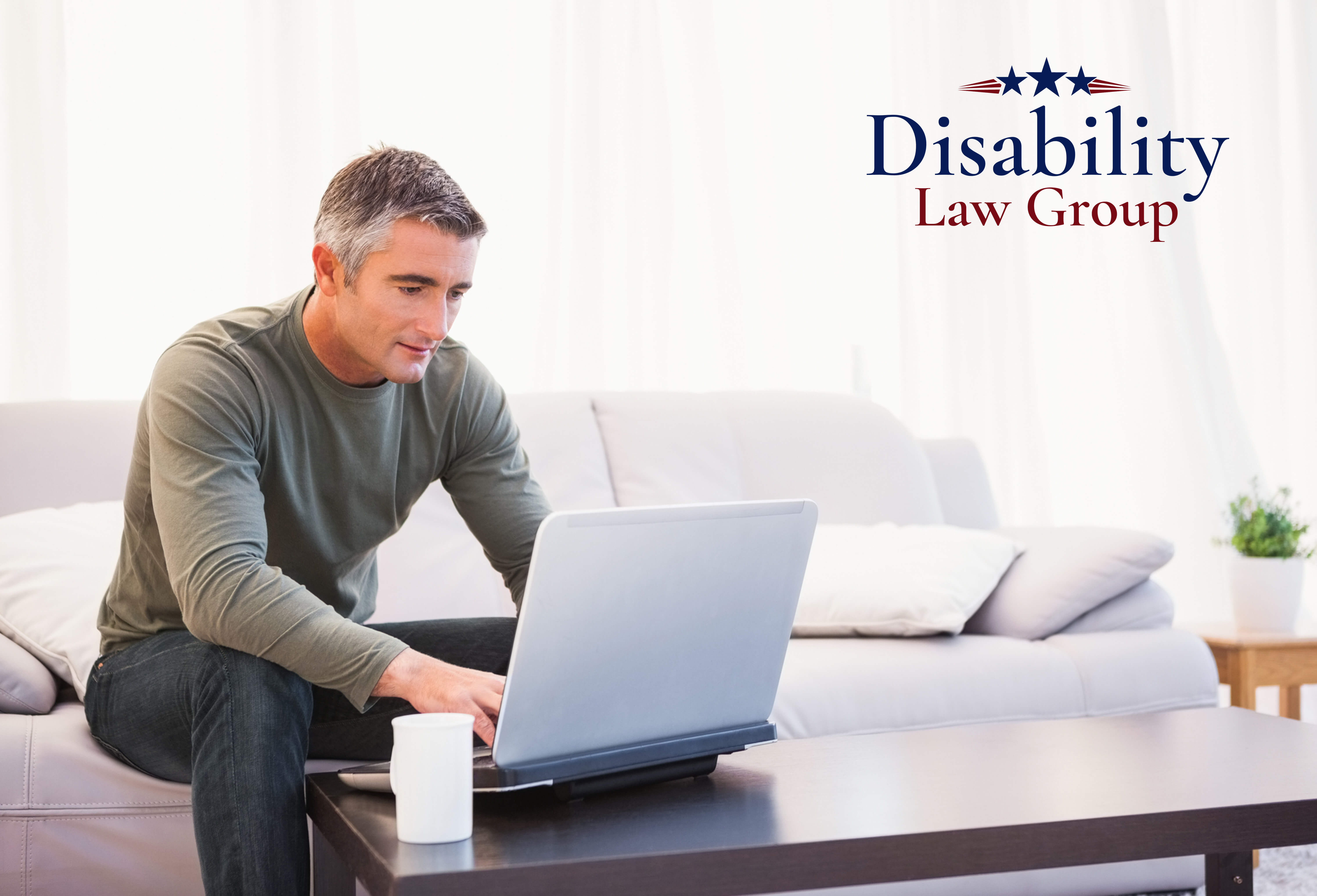 Man typing on computer in living room disability law group logo