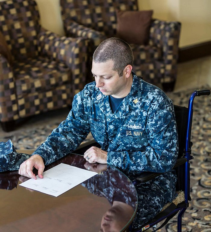 US Navy Officer Sitting In Wheelchair Reading Document.