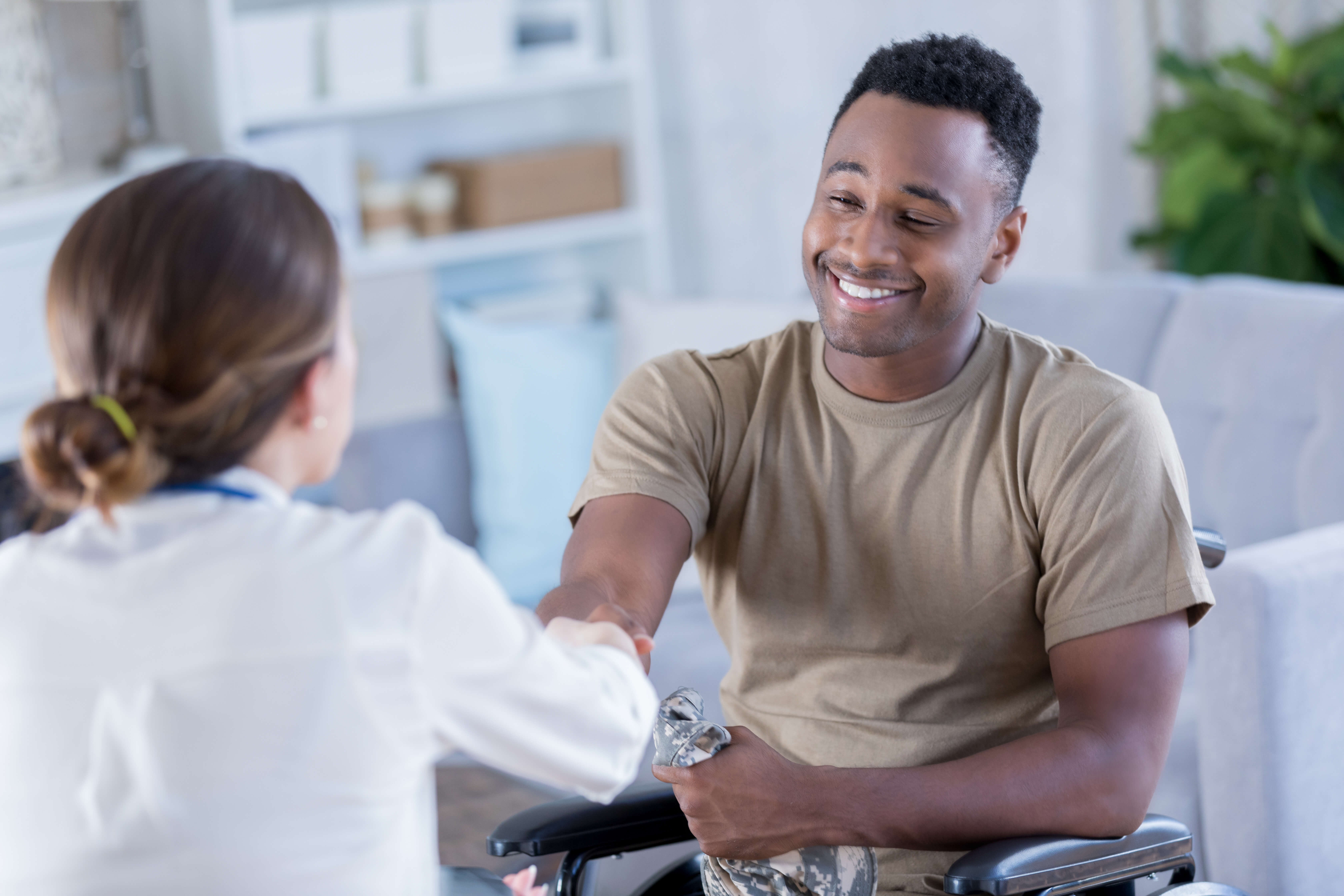 A wheelchair bound military office with PTSD, smiling as he is receiving medical assistance.