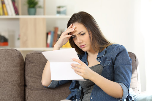 Concerned woman reading bad news in a letter sitting on a couch in the living room at home