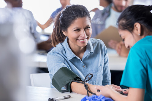 Young Hispanic female volunteer nurse checks a mid adult woman's blood pressure in free medical clinic.