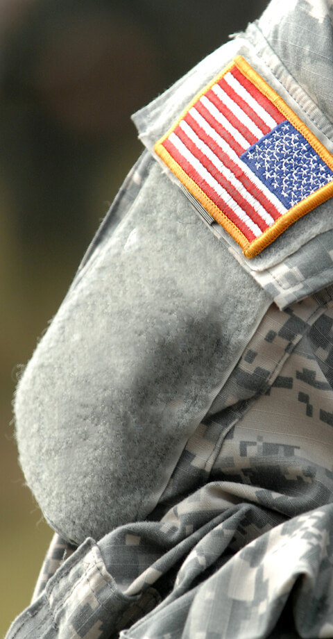 Persons shoulder in military uniform focused on American flag