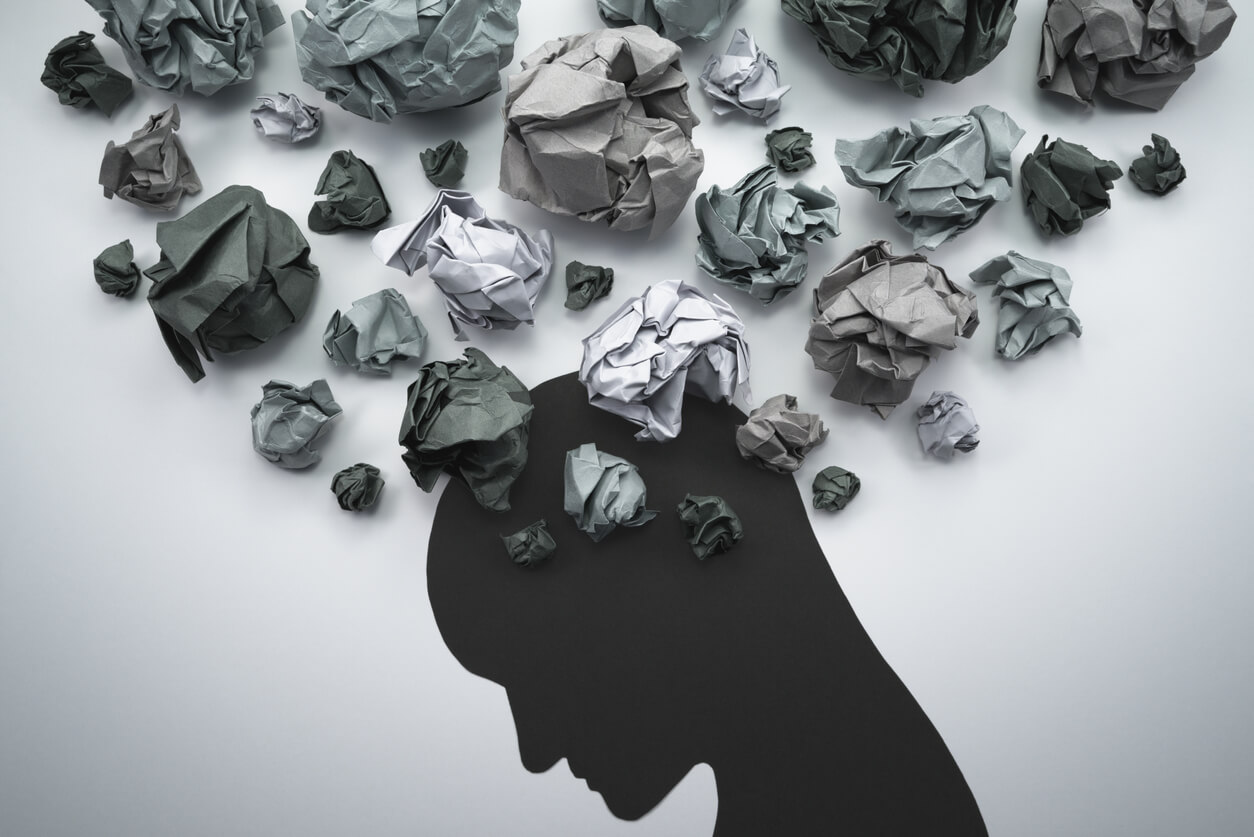 silhouette of person with clumped paper as thoughts